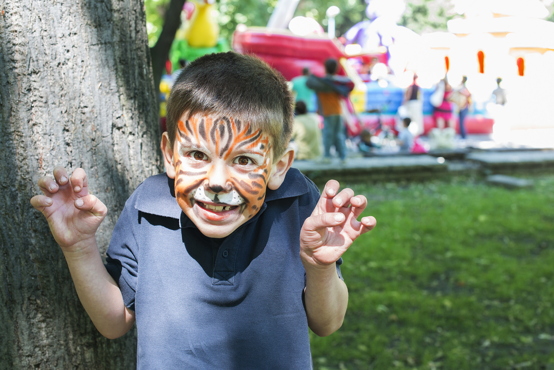 A young boy with his face painted like a tiger