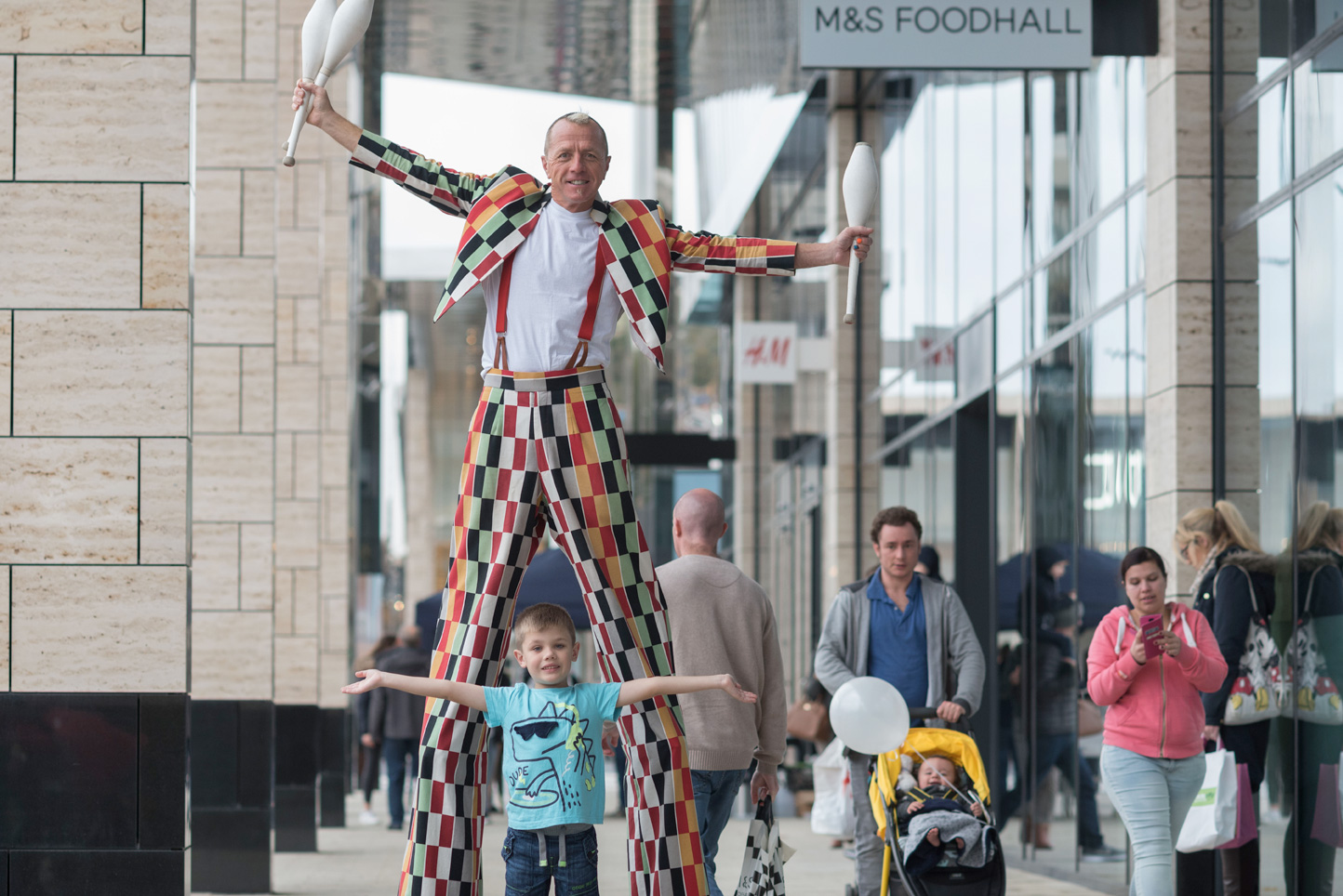 Clown on stilts shopping at retail park in Leeds