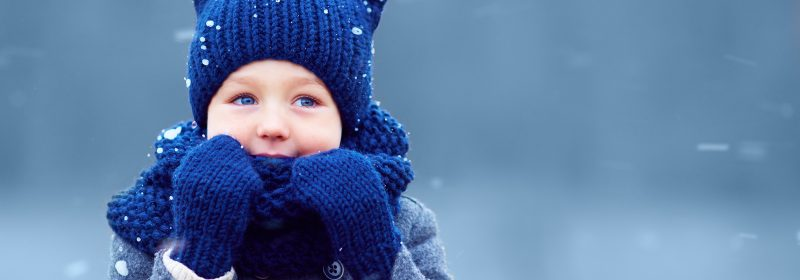 Cute boy with blue eyes wearing blue hat and glove at The Springs in Leeds